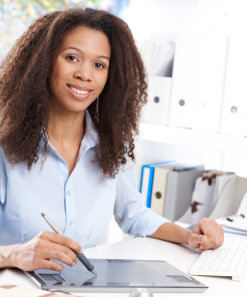 Smiling young business woman using drawing pad at desk