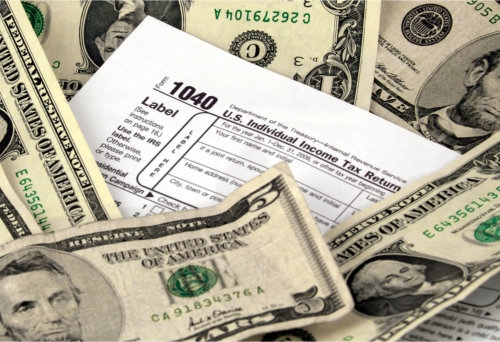 1040 u.s. individual income tax form surrounded by dollars